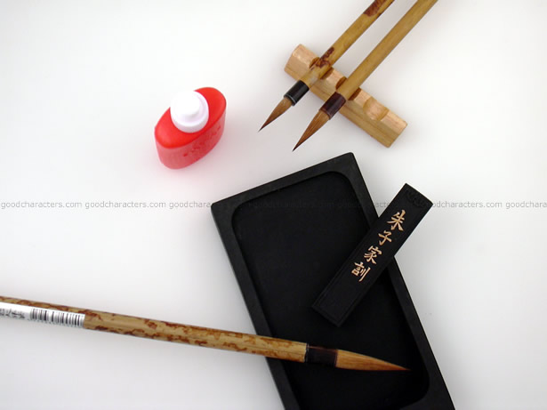 This calligraphy kit has three brushes, one ink stick, one ink stone, one brush rest, and one water dropper.